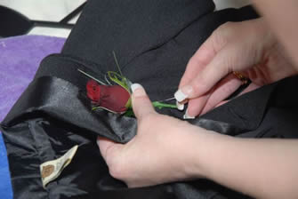 Much easier to pin on a buttonhole with the jacket off.  Left lapel. Stem pointing down.