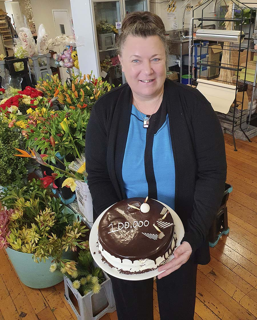 owner Best Blooms Florist Jo-Ann Moss with cake celebrating 100,000 flower orders.